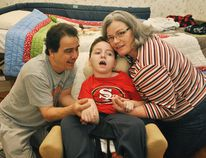 Robin Kilidjian, Ethan Kilidjian and Heather Mott are photographed in front of a specialized bed for their son, Ethan, inside their home in Chatham. Ethan has cerebral palsy and the bed was donated by the Mocha Cruisers Shrine Club.