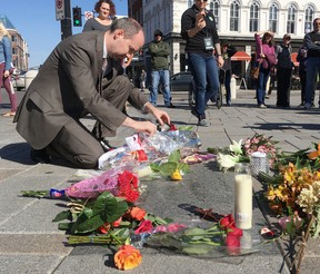 Elliot Ferguson/The Whig-Standard Kingston Mayor Bryan Paterson places flowers in Springer Market Square in memory of The Tragically Hip's lead singer Gord Downie on Wednesday.