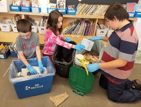 Reece Keyes, left, Paige Dewit and Demitri Nahwegahbo prepare for the waste audit at Walden Public School during Waste Reduction Week. Supplied photo