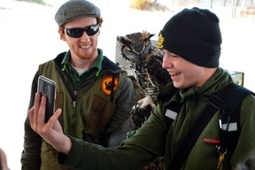 B. Davidson student Bryant Thorpe, right, takes a selfie with Jack the great horned owl and Matthew Morgan, a wildlife educator with the Canadian Raptor Conservatory. Morgan ran one of four exhibits along Port Stanley yesterday, a chance for students to learn about conservation at the Lake Erie Student Conference. (Louis Pin // Times-Journal)