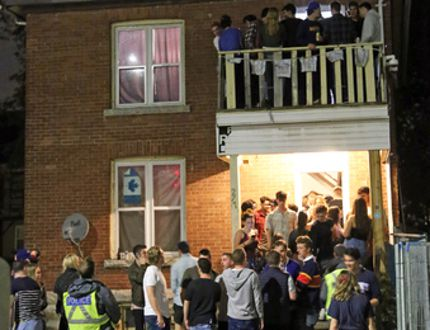Kingston Police peer up at a male on the peak of an Earl Street house during Queen's Homecoming last weekend. (Steph Crosier/The Whig-Standard)