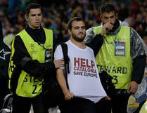 A man sporting a T-shirt demanding help for Catalonia is taken of the field by security during the UEFA Champions League group D soccer match between FC Barcelona and Olympiacos FC in Barcelona Wednesday. While some people in Quebec and Catalonia feel their region is homogeneous enough to separate from Canada and Spain, others would beg to differ. (JOSEP LAGO/AFP)