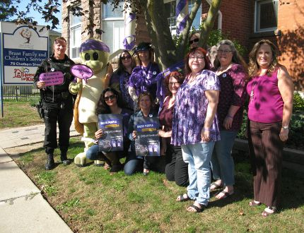 Brantford police Sgt. Jim Sawkins and Taylor the Turtle, from the Sexual Assault Centre of Brant, join staff from Brant Family and Child Services to demonstrate how they'll be spreading the Dress Purple Day message on Ont. 24. (Susan Gamble/The Expositor)