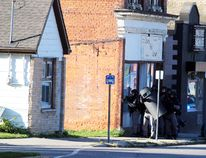 Heavily-armed police gather near a tactical truck deployed during a standoff just off the city's downtown on Friday. (Terry Bridge/Stratford Beacon Herald/Postmedia News)