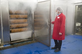 Pawel Zwerello, a food safety co-ordinator at Sikorski Sausages, opens the door of a sausage smoker at the company's London plant. Sikorski is part of Ontario's booming agri-food sector, one a new report suggests faces huge recruiting and hiring challenges to keep up with its growth. (DEREK RUTTAN, The London Free Press)