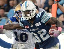 Toronto Argonauts running back James Wilder Jr. runs the ball and breaks a tackle against Winnipeg Blue Bombers linebacker Jovan Santos-Knox as linebacker Sam Hurl looks on during second half CFL football action in Toronto on Saturday, Oct. 21, 2017. THE CANADIAN PRESS/Nathan Denette