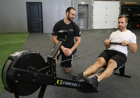 Co-owner and head coach Brad Hogue, of True North CrossFit, looks on as Joshua Bertollo goes through his exercise routine at the gym on Friday. (John Lappa/Sudbury Star)