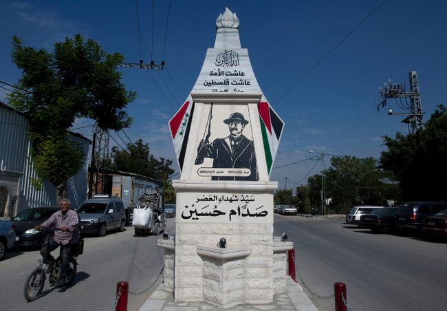 A Palestinian rides a bicycle past a monument commemorating the late Saddam Hussein in the West Bank city of Qalqiliya. (AP Photo/Nasser Nasser)