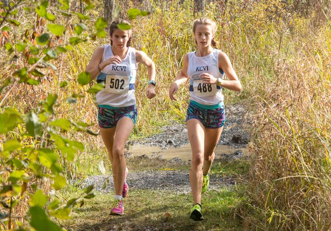 Anna Workman, left, and Mackenzie Campbell of the Kingston Blues run side by side through a muddy section of the course during the junior girls race at the Kingston Area Secondary Schools Athletic Association cross-country championships at the Little Cataraqui Creek Conservation Area this past Thursday. (Tim Gordanier/The Whig-Standard)