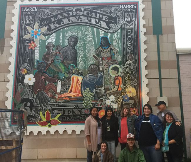 A group of artists, led by Brantford artist Dave Hind, celebrate the unveiling on Monday of La Landscape de Kanata, a public artwork they created. The work is mounted on the west wall of the Brantford Public Library. (Submitted Photo)