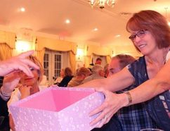 BRUCE BELL/The Intelligencer Mary Stever, one of the organizers of 100 People Who Care PEC, collects ballots at the Waring House on Monday evening. The Prince Edward Learning Centre was selected as the first recipient of close to $10,000 in donations.