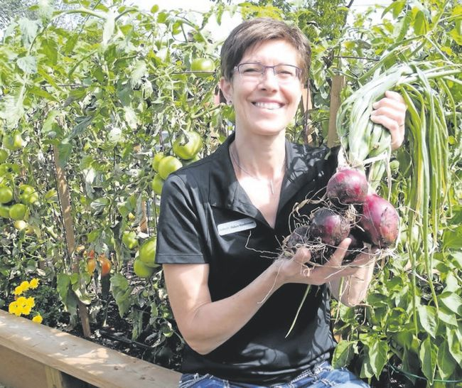 Debra Vandermeer of Simcoe shows off onions harvested in the summer from one of the community gardens established in the town by the local ecumenical group Church Out Serving. It's an example of Christians working to reverse divisions in the church that go back hundreds of years. (Monte Sonnenberg/Postmedia File photo)