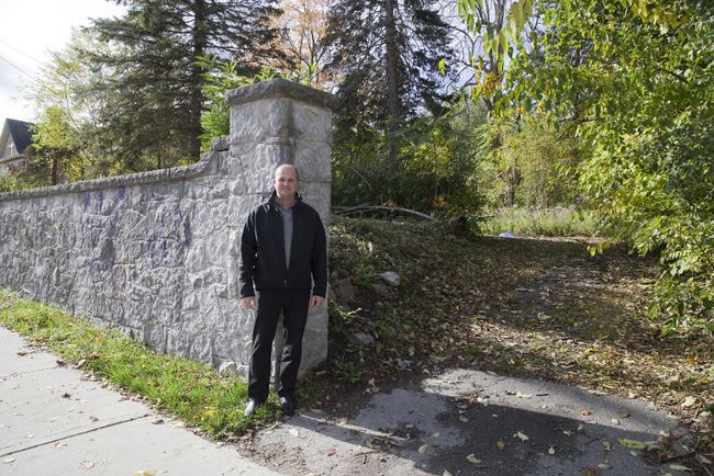 George Bikas of Drewlo Holdings stands at 661 Talbot St. in London where the company plans build an apartment building. He said the stone retaining wall won't be saved as plans are to make the surface level to the sidewalk. (DEREK RUTTAN, The London Free Press)