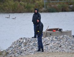 London police watch as water from a stormwater storage pond near Cudmore Crecent is drained Monday to allow investigators to search for evidence in the case of Josie Glenn. The remains of the 26-year-old London woman were found Friday in a home near the pond. A London man is charged with second-degree murder. (MORRIS LAMONT, The London Free Press)