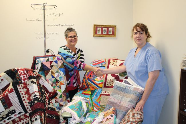 Angel Girard-Forget presents a number of finished quilts to Laurie Snook, R.N. chemo nurse. The quilts are to be given to patients using the chemo room at the Lady Minto Hospital. They are part of the Chemo Quilt Comfort Program that Girard-Forget has started.