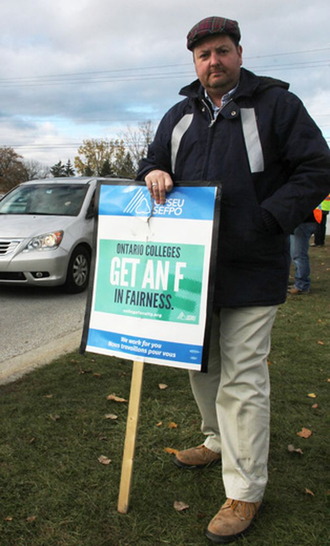 Mark Russell stands at the London Road entrance to Lambton College Monday where, he said, a motorist struck him. Russell, a computer studies professor, is one of thousands of striking college workers in the province. (Tyler Kula/Sarnia Observer/Postmedia Network)