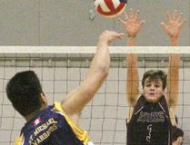 Northwestern's Jared Larder tries to block St. Mike's Mark Manzano during the senior boys volleyball semifinal Tuesday at the Stratford Agriplex. St. Mike's won in three sets. (Cory Smith/The Beacon Herald)