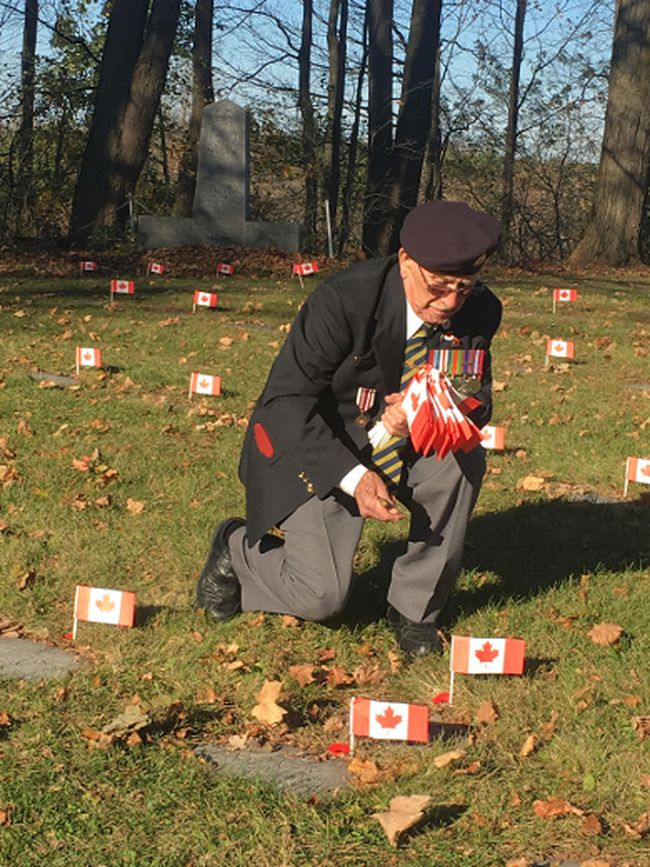Ken MacGillivray decorates the grave of a veteran Wednesday at the Legion's plot at the Anglican cemetery. (Photo by Karen Miller)