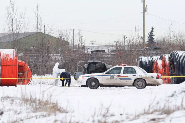 Investigative units survey the scene of a charred Jeep in Strathcona County in 2014, when a 30-year-old man was killed in the local industrial park.