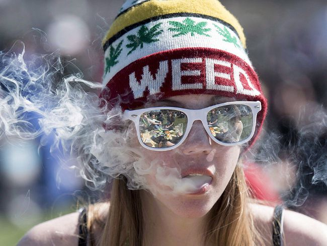 A woman exhales while smoking a joint during the annual 420 marijuana rally on Parliament hill on Wednesday, April 20, 2016 in Ottawa. THE CANADIAN PRESS/Justin