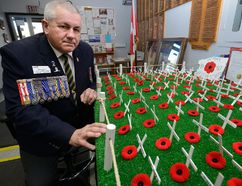 Brian Harris, Southwest Ontario Legion Commander looks over the rows of crosses in the lobby of the Victory Legion in London, representing members who died in action. (MORRIS LAMONT, The London Free Press)