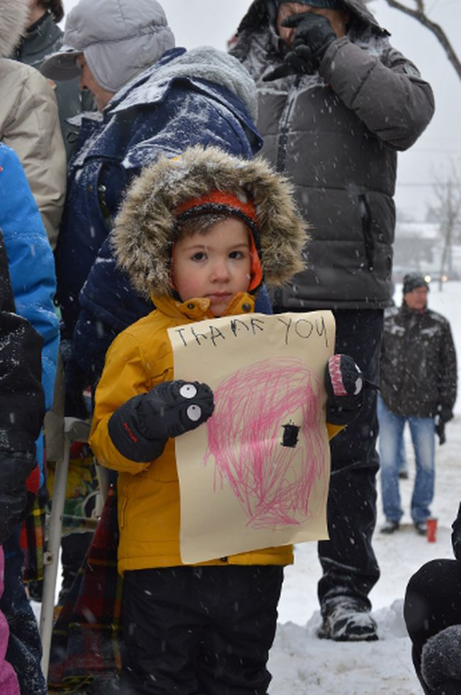 Jack Stefanic watches the Remembrance Day ceremony in Timmins carefully. The four-year-old brought a homemade sign to thank veterans for their service and sacrifice.