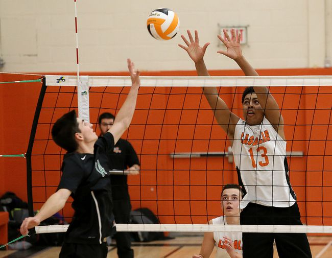 Miguel Mrochek, left, of Horizon Aigles, attempts to tip the ball past Nathan Scully, of Lasalle Lancers, during senior boys volleyball final action at Lasalle Secondary School in Sudbury, Ont. on Saturday November 11, 2017. John Lappa/Sudbury Star/Postmedia Network