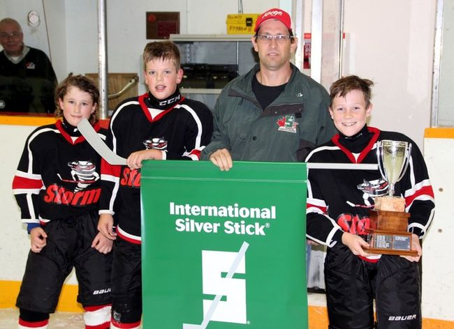 Sean Chase/Daily Observer  The Valley Storm captured the Pembroke International Silver Stick Atom 'C' title Sunday shutting out the Muskrat Voyageurs 3-0. Here tournament convenor Rodney Stewart presents the championship banner to team captains (left to right) Wyatt Hicks, Carter McIntyre and Aydan Flegal.