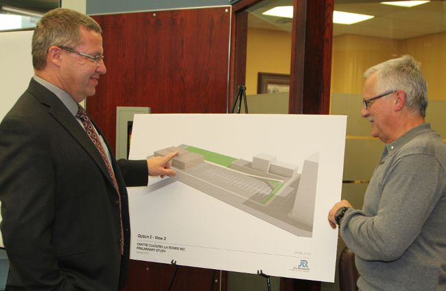 Ludger Cloutier, new building project leader for the Centre culturel La Ronde, right, chats with Michel Fecteau, chairman of the board of directors of La Caisse populaire de Timmins, while viewing a conceptual design for the new centre. On Monday, La Caisse donated $500,000 towards the project.
