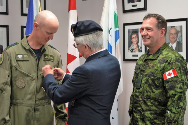 Col. Paul Doyle, commander of 4 Wing Cold Lake, was the first to receive a poppy for the Cold Lake Poppy Campaign. He accepted the poppy from Pat Henderson, second vice-president for the Cold Lake Legion Branch No. 211 on Oct. 26. Acting Wing Chief Warrant Officer Frank Dwyer (right) looks on.