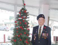 World War II veteran Carm Colvin, who is a resident of the Riverview Legion Apartments in Carman, stands next to Riverview's latest tradition in honour of Remembrance Day and all those who have served. The tree is decorated with 100 poppies. (EMILY DISTEFANO)