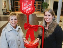 Salvation Army volunteer Carol Roche, left, and Christmas Kettle co-ordinator Maria Sadowy pose with one of the 19 Christmas Kettles on Tuesday at the Salvation Army Citadel in Kingston. The annual campaign launch is starting this Friday at the Cataraqui Centre and organizers are hoping to raise $310,000 for the variety of local programs and services throughout the year. (Julia McKay/The Whig-Standard)