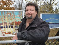 """Festival of Northern Lights chair Jamie Walpole on Wednesday with two of three Tom Thomson paintings which have been printed on plexiglass and lit from behind and placed in Queen's Park for the 30th annual holiday lights festival which opens Saturday. Paintings shown here are """"April in Algonquin Park, Spring 1917"""" (left) and """"Northern Lights, Fall 1915"""". (Scott Dunn/The Sun Times)"""