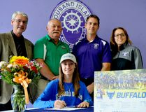 Lily Meek signs a copy of her athletic scholarship at the University of Buffalo at Thousand Islands Secondary School on Wednesday. Behind her, from left, are TISS principal Terry Gardiner, Legion track coach Bob Tucker and TISS coaches Randy Givogue and Christine Grzela. (RONALD ZAJAC/The Recorder and Times)