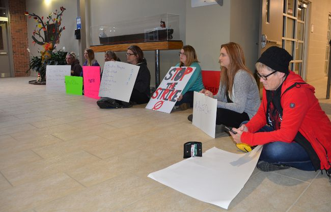 Students take part in an #AssToClass rally in the lobby at Georgian College's Owen Sound campus on Thursday. At right, student Dona Ashcroft checks for the latest news on the college faculty strike. (Rob Gowan The Sun Times)