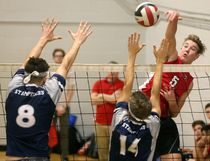 Stratford Central's Evan Falardeau hits over the combined block of Parkside's Josh Hare and Christian Coombes during their WOSSAA double-A senior boys volleyball semifinal Thursday at South Secondary in London. Central won in four sets and went on to take the gold medal. (Mike Hensen/Postmedia Network)