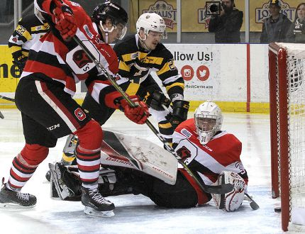 Kingston Frontenacs' Tyler Burnie gets the puck past Ottawa 67's goalie Cedrick Andree as Kevin Bahl comes in late to help during Ontario Hockey League action at the Rogers K-Rock Centre on Sunday. (Ian MacAlpine/The Whig-Standard)