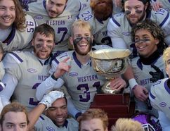 Western Mustangs players celebrate with the trophy after their dominating 81-3 win over the Acadia Axemen in the Uteck Bowl on Saturday. (THE CANADIAN PRESS)