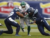 Roughriders wide receiver Marcus Thigpen is stopped by a pair of Toronto Argonauts defenders in Sunday's East final. THE CANADIAN PRESS/Mark Blinch