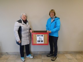 Crystal Crowley (L) and Colleen McGregor are the lead organizers of this year's Annual Christmas Bureau in Goderich, running out of St. Peter's Church. Seen here dropping off one of the several donation boxes around town. (Kathleen Smith/Goderich Signal Star)