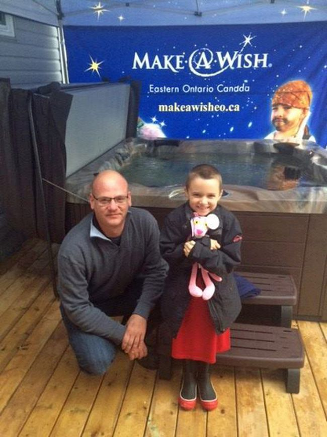 Pembroke's Blok Pools and Hot Tubs adopted and sponsored Caitlin's wish. Pictured here, Blok Pools and Hot Tubs' Matthew Fraser poses with Caitlin and her new hot tub.