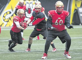 Laval Rouge et Or quarterback Hugo Richard hands off to Alexis Cote during practice Thursday in Hamilton ahead of the Vanier Cup against the Western Mustangs on Saturday at Tim Hortons Field. (The Canadian Press)