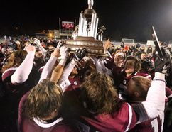 Jubilant South Lions players surround the prized trophy as the celebrate their WOSSAA senior football victory over CCH Crusaders at TD Stadium in London Thursday. The Lions beat CCH 14-1 to claim the title. In the junior final, played earlier in the day, Parkside Stampeders defeated the Crusaders 35-7. (MIKE HENSEN, The London Free Press)
