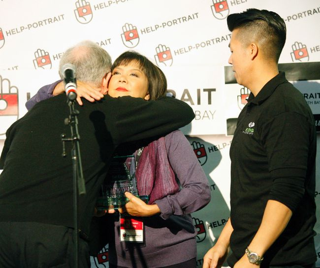 John Wallace hugs Helen Eng, while her son, Dion, looks on during the Help Portrait event Sunday in North Bay. Wallace presented the two with a plaque in honour of Ed Eng, her husband and his father, who died in the spring. Eng, a local photographer, brought the event to North Bay eight years ago. Gord Young/The Nugget.