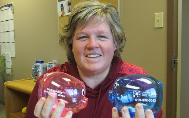 Paula McKinlay, with the Canadian Cancer Society's Sarnia-Lambton office, holds plastic piggy banks local residents are being asked to fill with donations over the holidays for the Wheels of Hope cancer patient transportation program. The fundraiser is called Pigs of Hope. (Paul Morden/Sarnia Observer/Postmedia Network)