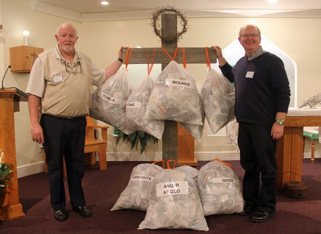 Pictured here, Archdeacon Ron Corcoran (left) and St. Luke's Anglican Church Pastor Tim pose next to a display they set up during the Wounded Healers Conference, with the garbage bags representing all of the past wounds that we carry and which negatively impact our present and future - and for which we can find healing through Christ.