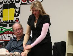 Morden Massage Therapy Centre owner Linda Menzies demonstrates lymph fluid drainage and a compression wrap on SCCR treasurer Wes Schroeder. (LAUREN MACGILL, Morden Times)