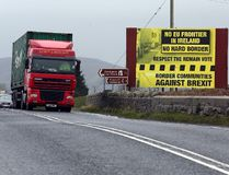 This file photo taken on January 30, 2017 shows traffic crossing the border into Northern Ireland from the Irish Republic next to a poster protesting against a hard brexit near Dundalk on January 30, 2017. The fallout of Brexit is not only about trade and the economy, Brexit is also about keeping the peace, a peace that must not be taken for granted two decades after the Good Friday agreement erased the border between British-ruled Northern Ireland and the Republic of Ireland, but still struggles to bridge communities. (AFP PHOTO / Paul FAITH)