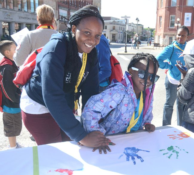 Uganda's Nagawa Cissy helps daughter Kirabo make a hand print during the World Festival of Children's Theatre in this Beacon Herald file photo. In response to the city hosting this event in June 2016, the International Amateur Theatre Association has set up the Stratford Perth Youth Arts Fund through the Stratford Perth Community Foundation. (Beacon Herald file photo)