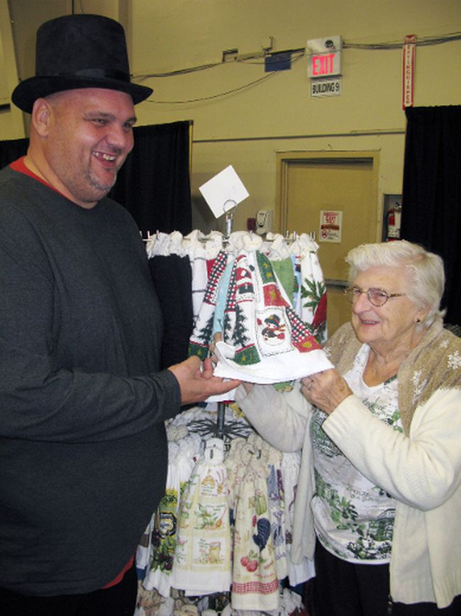 Dan Avey of YFC/Youth Unlimited Norfolk and Donna Davies of St. Thomas show off one of the tea towels Davies was selling at the annual Dickens Christmas Craft Show in Simcoe on the weekend. The craft show is a major fundraiser for the youth organization. VINCENT BALL/Postmedia News